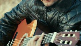 Молодой человек играя гитару около реки ретро видеоматериал