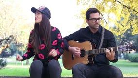 Молодой человек играя гитару пока красивая женщина сидя рядом с ним акции видеоматериалы