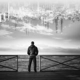 Молодой человек играя главные роли на море с городом в небе Стоковое Изображение