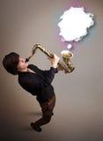 Молодой человек играя на саксофоне с космосом экземпляра в белом облаке Стоковая Фотография