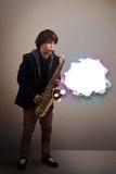 Молодой человек играя на саксофоне с космосом экземпляра в белом облаке Стоковое фото RF