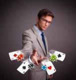 Молодой человек играя с карточками и обломоками покера Стоковая Фотография