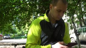 Молодой человек играя телефон, на заднем плане зеленых деревьев акции видеоматериалы