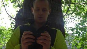 Молодой человек играя телефон, на заднем плане зеленых деревьев видеоматериал