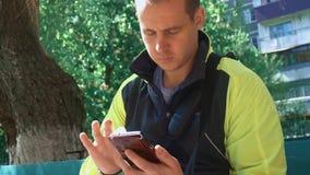 Молодой человек играя телефон, на заднем плане зеленых деревьев сток-видео