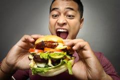 Молодой человек имеет большое желание съесть бургер стоковая фотография rf