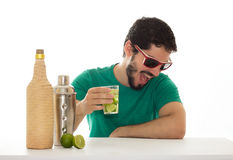 Молодой человек имея потеху на таблице бара, выпивая спиртное cockt Стоковые Изображения