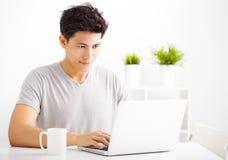Молодой человек используя компьтер-книжку в живущей комнате стоковая фотография
