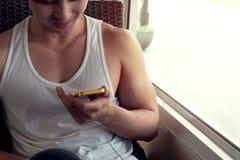 Молодой человек используя мобильный телефон с отправляя СМС сообщением Стоковые Фотографии RF