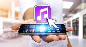 Молодой человек используя современный мобильный телефон для того чтобы слушать музыка Стоковое фото RF