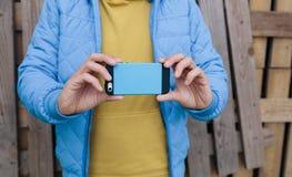 Молодой человек используя умный телефон мобильный телефон польз человека для того чтобы принять фото Стоковая Фотография
