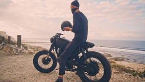 Молодой человек идет к его мотоциклу, сидит на ем и кладет шлем для того чтобы пойти на путешествие через океан движение медленно сток-видео