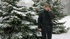 Молодой человек идет на лес зимы и говорить на телефоне Большие снежности Он останавливает и кончает переговор Человек внутри видеоматериал