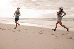 Молодой человек и женщина бежать в утре на пляже Стоковая Фотография