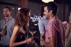 Молодой человек и женщина говорят и смеются над на партии, взгляде со стороны Стоковое Изображение RF