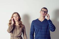 Молодой человек и женщина говоря на телефоне Стоковые Изображения RF