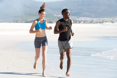 Молодой человек и женщина делая бежать работать на пляже Стоковое фото RF
