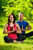 Молодой человек и женщина делая йогу в солнечном лете Стоковые Изображения RF
