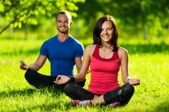 Молодой человек и женщина делая йогу в солнечном лете Стоковое Фото