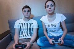 Молодой человек и женщина играя видеоигры Стоковые Изображения RF