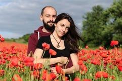 Молодой человек и женщина имея дату в поле маков Стоковое фото RF