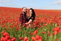 Молодой человек и женщина имея дату в поле маков Стоковая Фотография RF