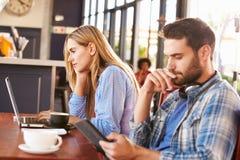 Молодой человек и женщина используя компьютеры на кофейне Стоковое Фото