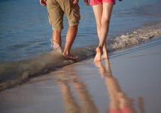 Молодой человек и женщина идя вдоль берега моря Стоковое Фото
