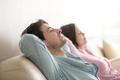 Молодой человек и женщина ослабляя, глаза закрыли, взгляд со стороны, внутри помещения Стоковое Изображение RF