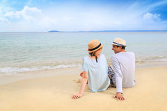 Молодой человек и женщина ослабляя на пляже Стоковые Фотографии RF