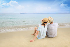 Молодой человек и женщина ослабляя на пляже Стоковое Фото