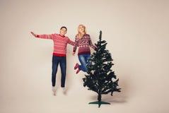 Молодой человек и женщина перескакивая высоко в воздухе Стоковые Изображения