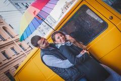 Молодой человек и женщина при длинные волосы обнимая под ярким покрашенным зонтиком усмехаясь на фоне желтого фургона стоковая фотография