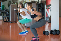 Молодой человек и женщина при штанга изгибая мышцы и делая плечо для того чтобы отжать сидение на корточках в спортзале Стоковое Фото