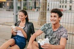 Молодой человек и женщина сидя outdoors и усмехаясь Стоковая Фотография RF