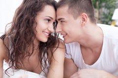 Молодой человек и женщины в влюбленности лежа на кровати Стоковое Изображение