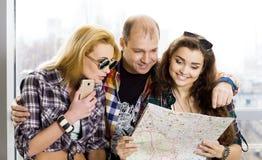 Молодой человек и 2 женщины смотря карту европейцы amicability Собранный в экскурсии Конец-вверх стоковое изображение