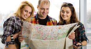 Молодой человек и 2 женщины смотря карту европейцы amicability Собранный в экскурсии Конец-вверх стоковое фото rf