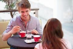 Молодой человек и кофе женщины выпивая внешний и имея болтовню дальше Стоковое Фото