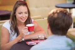 Молодой человек и кофе женщины выпивая внешний и имея болтовню дальше Стоковые Изображения RF