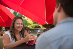Молодой человек и кофе женщины выпивая внешний и имея болтовню дальше Стоковые Изображения