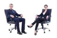 Молодой человек и красивая женщина в деловых костюмах сидя на offic Стоковая Фотография