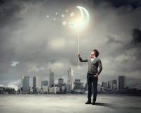 Молодой человек и символ луны Стоковая Фотография RF