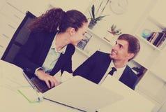 Молодой человек и усмехаясь сотрудники женщины говоря в твердом офисе Стоковое Фото