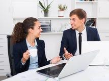 Молодой человек и удовлетворенные сотрудники женщины говоря в твердом офисе Стоковое Изображение