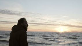Молодой человек идя в берег моря одного и смотря на волнах Мужчина наслаждаясь заходом солнца на пляже сток-видео