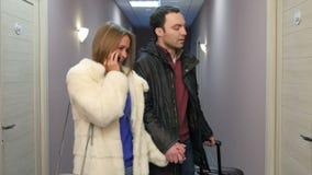 Молодой человек идя вдоль залы гостиницы с чемоданом пока его подруга говоря на телефоне видеоматериал
