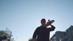 Молодой человек идя и держит скейтборд на плече видеоматериал