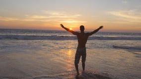 Молодой человек идя на воду океана на пляже на заходе солнца и поднятых руках Sporty парень стоя на море берег и ослабляя Стоковые Фотографии RF