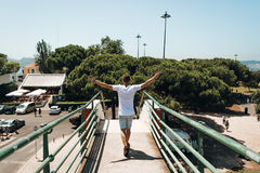 Молодой человек идя с оружиями распространил с свободой стоковые фото